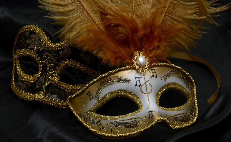 A white carnival mask covered in musical symbols and extravagant feathers sits in front of a more subdued, black carnival mask.