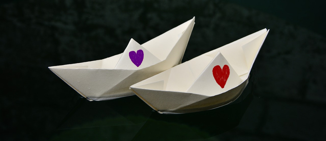 Two paper boats, one with a red heart drawn on it, the other with a purple heart drawn on it