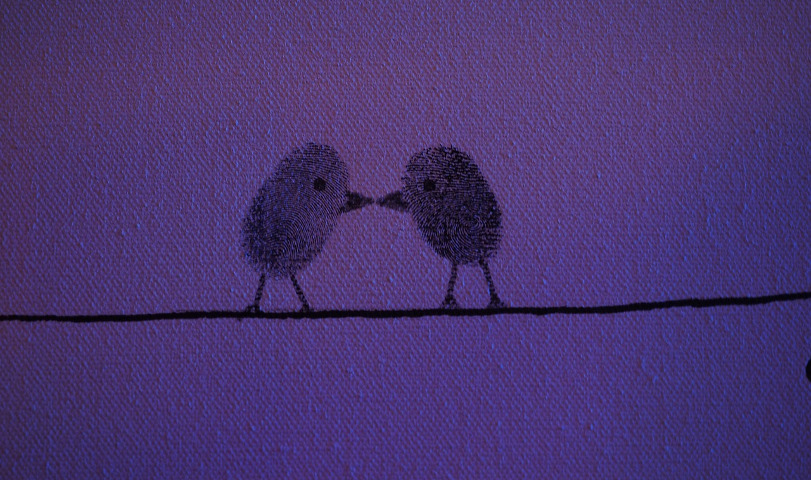 On a purple background, two birds made out of thumbprints hesitantly touch beaks