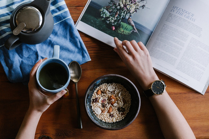 A breakfast table with cereal, tea, and an open magazine
