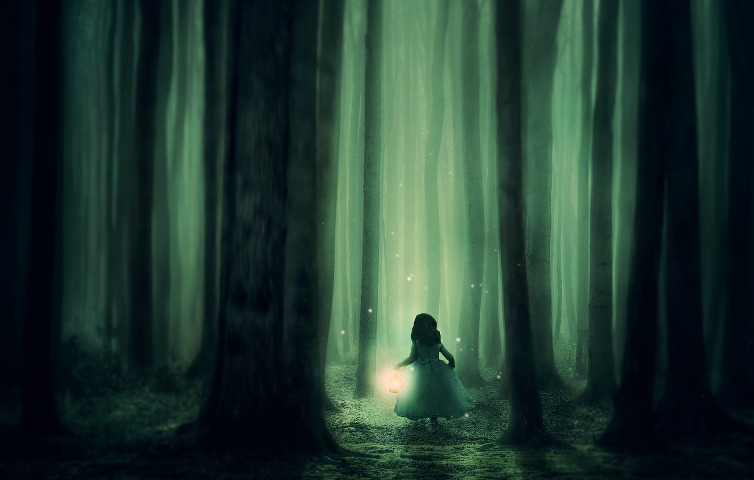 Girl with a lantern finding her way through a dark forest