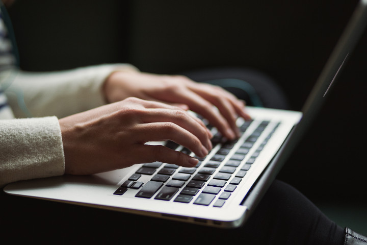 Close up on hands typing at a computer keyboard