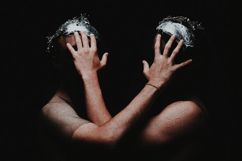 Two figures in the dark cover each other's faces with their hands