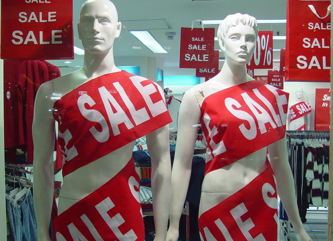 "Male and female mannequins, naked but wrapped in banners that say ""Sale"""