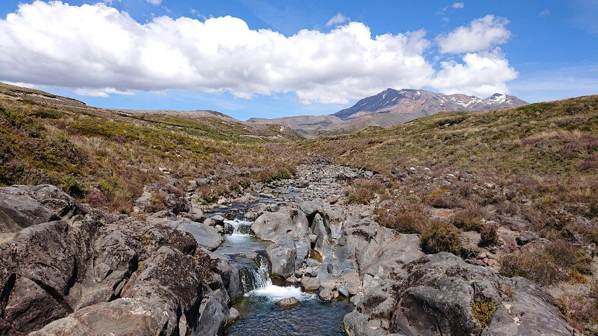 A rulling landscape of scrub, with mountains in the distance and a stream flowing over rapids in the foreground