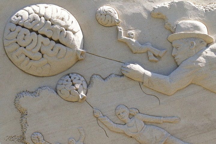 Sand sculpture of several people being lifted off their feet while hanging on strings attached to baloons that look like brains. One looks happy about it, another distressed, another determined.