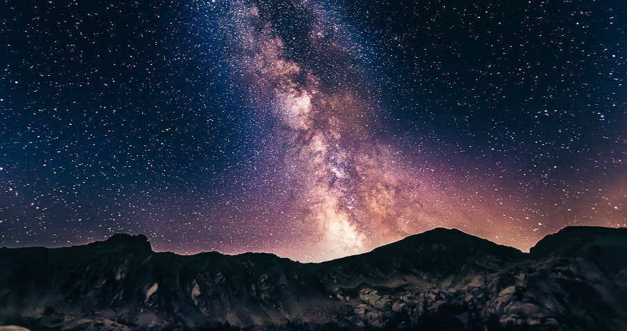 A starry backdrop behind dark mountains