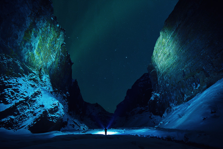 A tiny figure standing alone in a canyon at night, surrounded by towering cliffs, under the nothern lights.