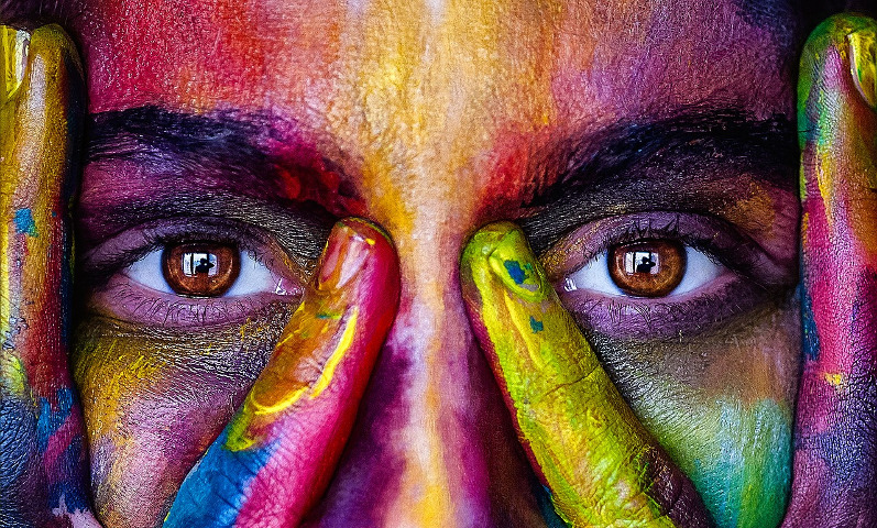 Close-up of a face looking straight at you, covered in rainbow-coloured paint