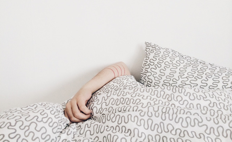 Person buried under a doona and pillows, only their arm sticking out