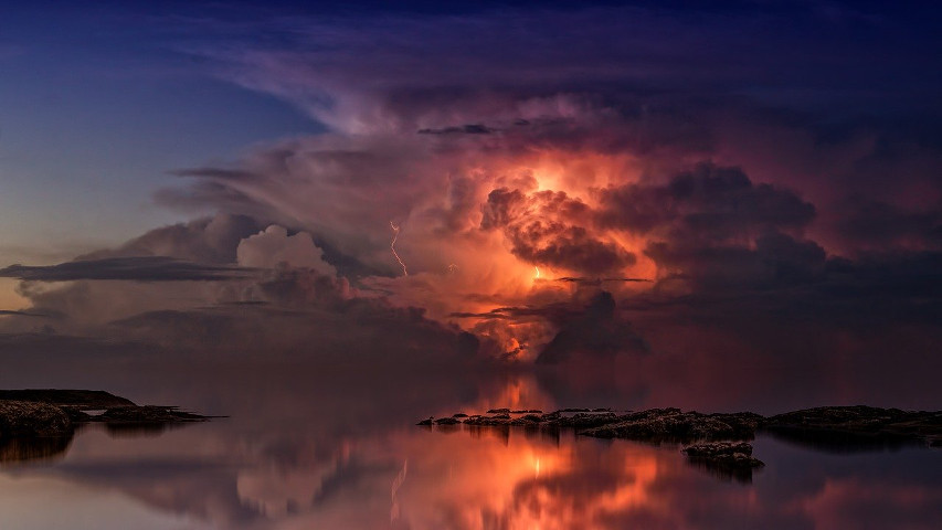A distant thunderstorm looming over a quiet ocean