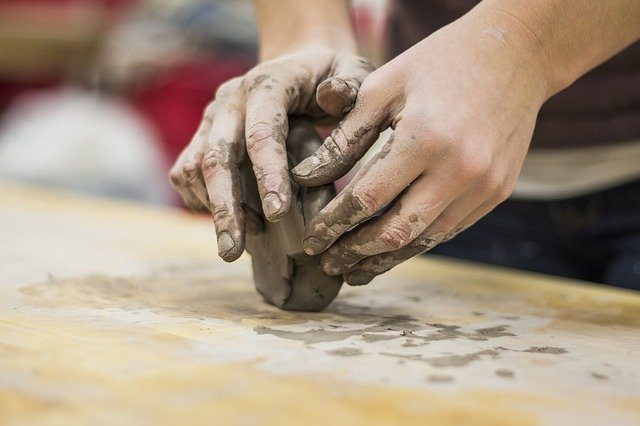 Two hands working with a lump of clay