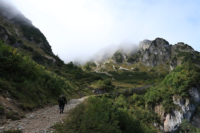A lone walker at the base of a mountain range