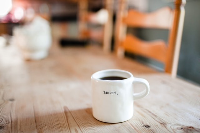 "A white coffee mug sits on a wooden table; printed on it is the word ""begin"""