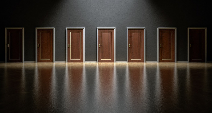 A dark wall containing several identical doors