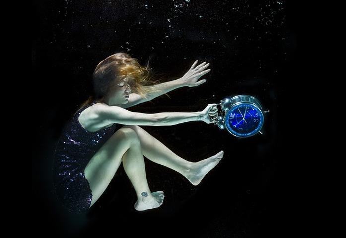 Woman sinking through black water, holding a clock