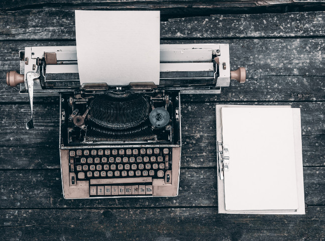 Typewriter with a blank page on a dark background