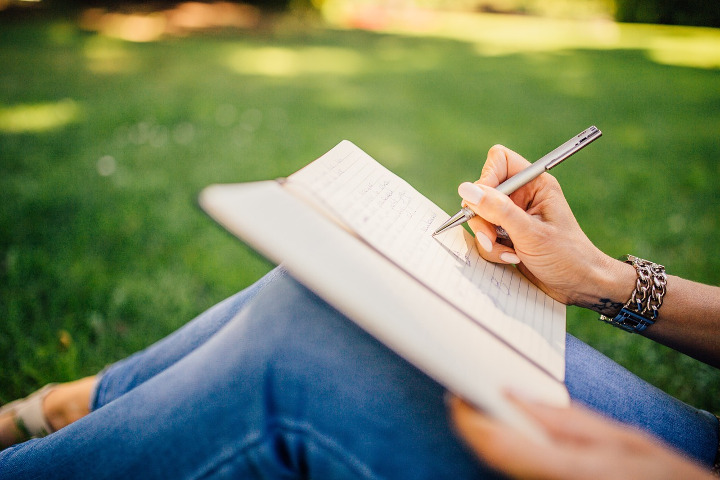 Someone sitting in a park with a notepad and pen