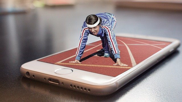 A mobile phone lies face-up on a table, with an image of a race track on the screen. A tiny, three-dimensional athlete crouched on top of the phone at the starting line of the race.