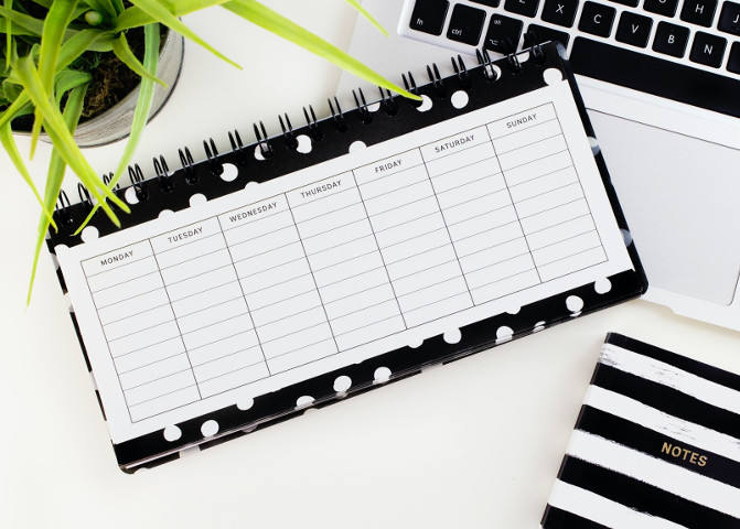 Black and white weekly planner on a desk
