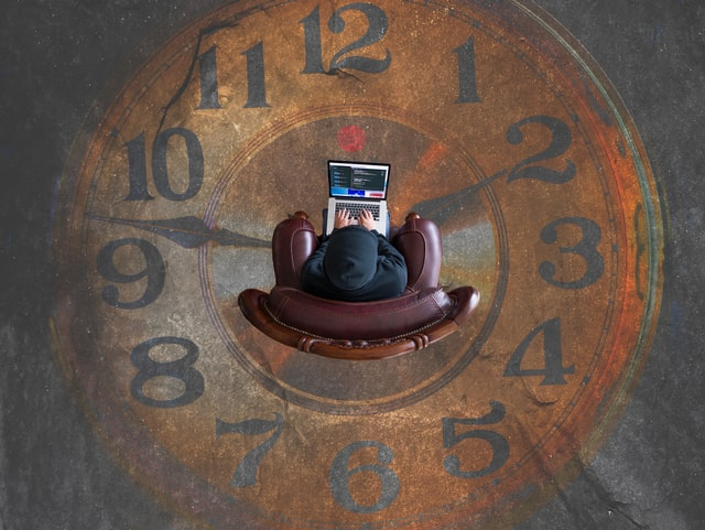 Figure in a hoodie sitting in an armchair working on a laptop, against the backdrop of a faded, brown, analog clock